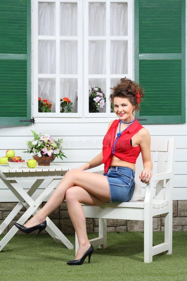 La jeune femme s'assied à la table en bois blanche avec des fruits photos stock