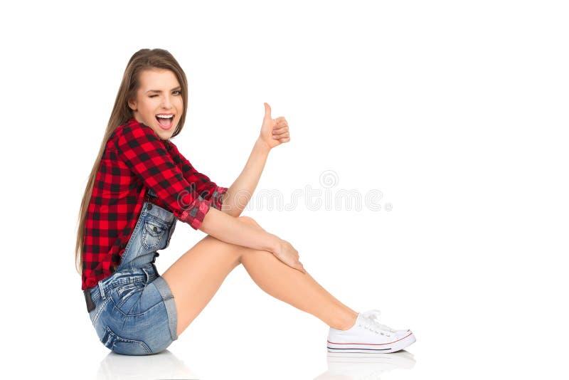 La jeune femme s'assied montrant le pouce et cligner de l'oeil photographie stock libre de droits