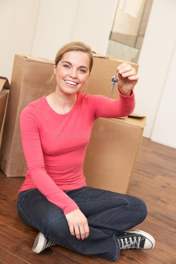 La jeune femme s'assied sur l'étage retenant une clé dans elle image stock