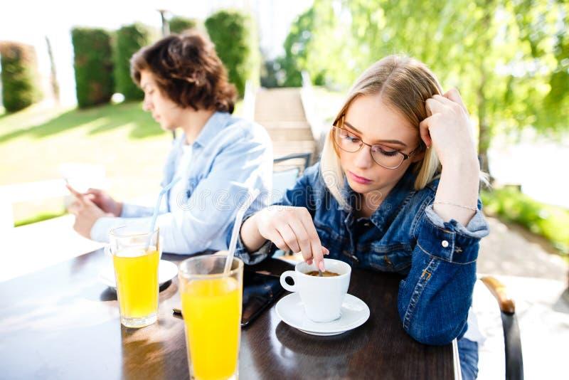 La jeune femme s'ennuie parce que son ami dépensant trop de Tim image libre de droits