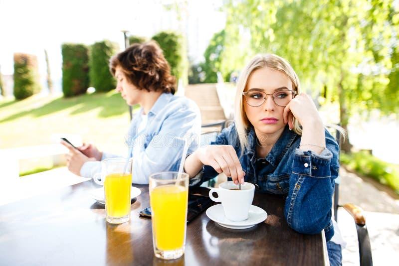 La jeune femme s'ennuie parce que son ami dépensant trop de Tim photos libres de droits