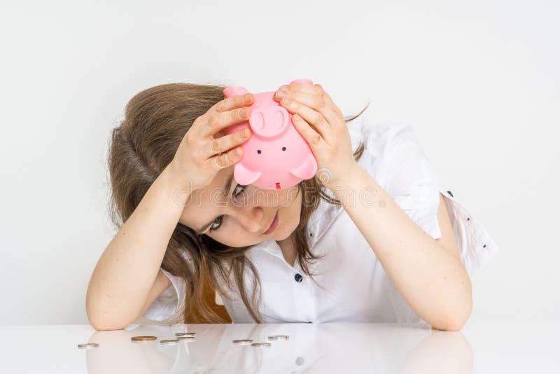 La jeune femme sans l'argent regarde à la banque porcine vide d'argent photo libre de droits