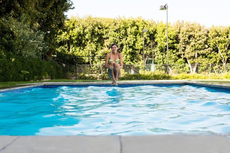 La jeune femme sautant dans la piscine image libre de droits