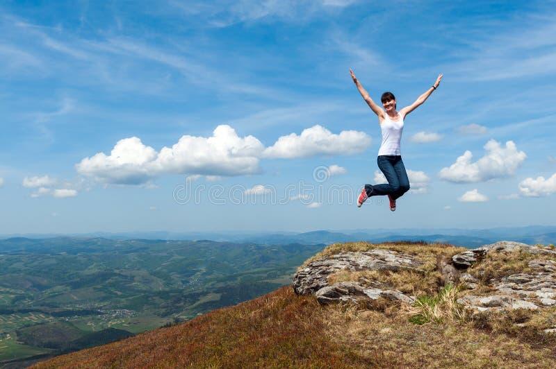 La jeune femme sautant sur un fond des montagnes photo stock