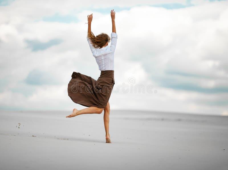 La jeune femme saute sur le sable dans le désert images stock