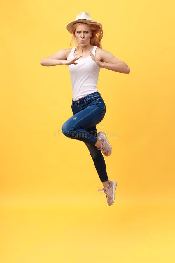 La jeune femme sautent le karaté donnant un coup de pied dans le plein vol d'isolement au-dessus du fond jaune d'été photographie stock