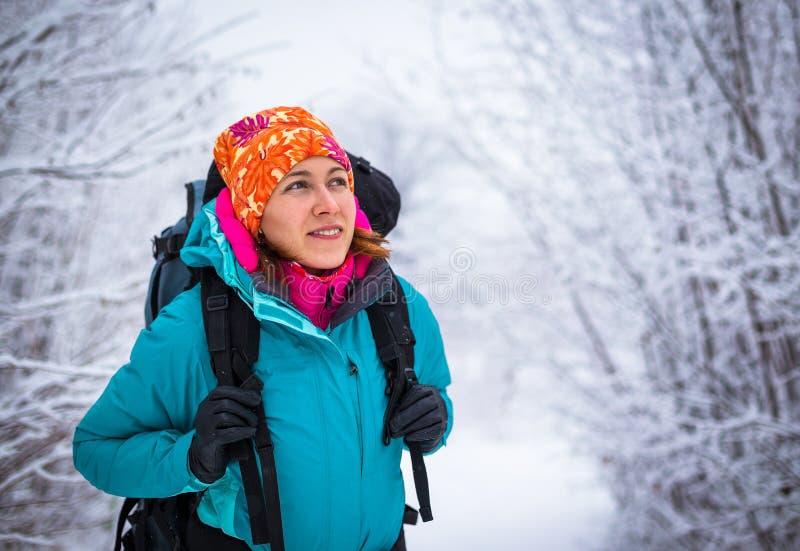 La jeune femme se baladante apprécient la nature dans la belle forêt d'hiver images stock