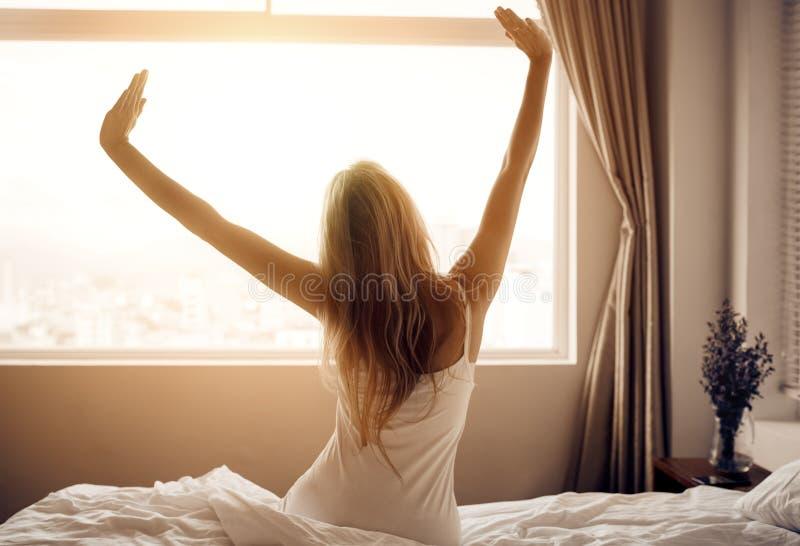 La jeune femme se réveillent dans la chambre à coucher photo stock