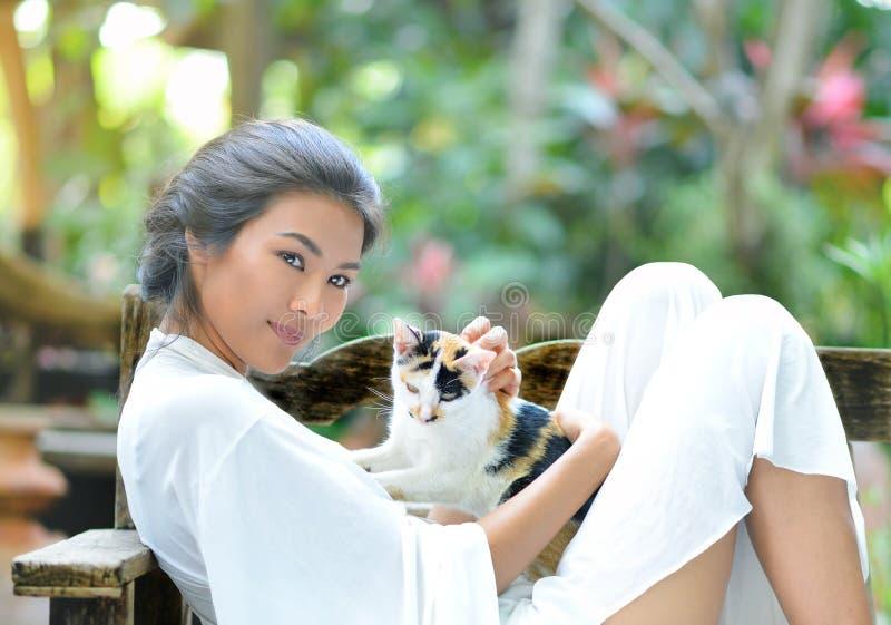 La jeune femme se repose avec un chat photographie stock