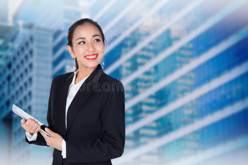 La jeune femme se tenant utilisant la tablette de pavé tactile, modèle est une Asiatique photographie stock