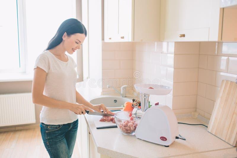 La jeune femme se tient dans la cuisine et coupe la viande en morceaux Elle le dispose pour grinded Il y a cuvette avec différent photos libres de droits