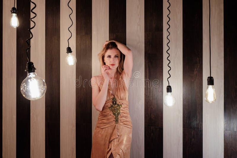 La jeune femme se tient dans la chambre noire avec beaucoup de lampes lumineuses image libre de droits