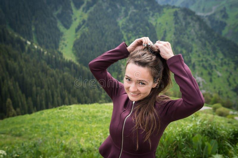 La jeune femme se tient en parc national sur le fond des montagnes vertes image stock