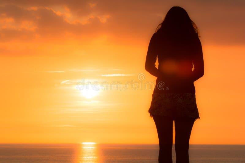 La jeune femme se tient regardante à la mer le coucher du soleil photos stock
