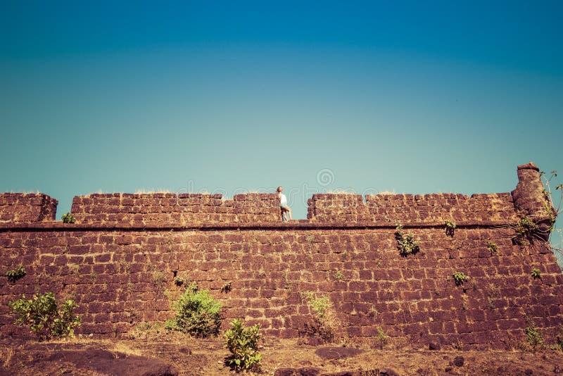 La jeune femme se tient sur le mur de briques du vieux fort image stock