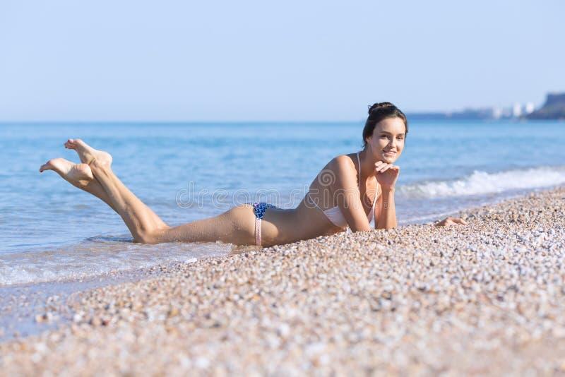La jeune femme se trouvant sur l'avant sur des cailloux s'approchent de la mer images stock
