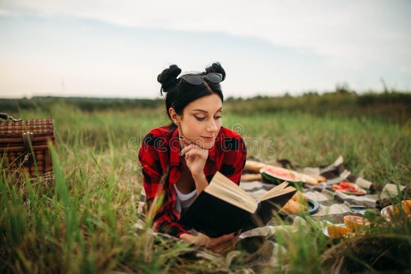 La jeune femme se trouve sur le plaid et lit le livre, pique-nique images libres de droits