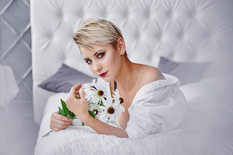 La jeune femme se trouve sur un lit avec un bouquet des camomiles images stock