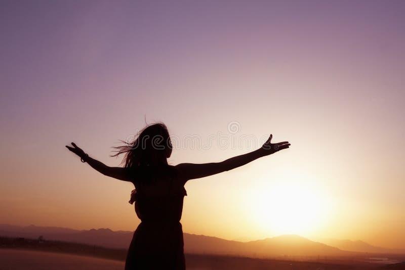 La jeune femme sereine avec des bras a tendu faire le yoga dans le désert en Chine, silhouette photographie stock