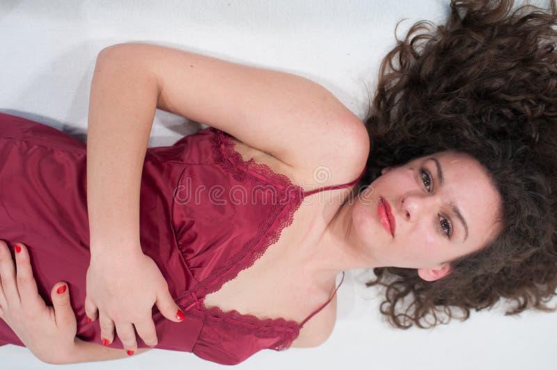 La jeune femme sexy avec les cheveux bouclés, le mensonge en buste, le petit groupe des cheveux onduleux et bouclés et la femme d images libres de droits