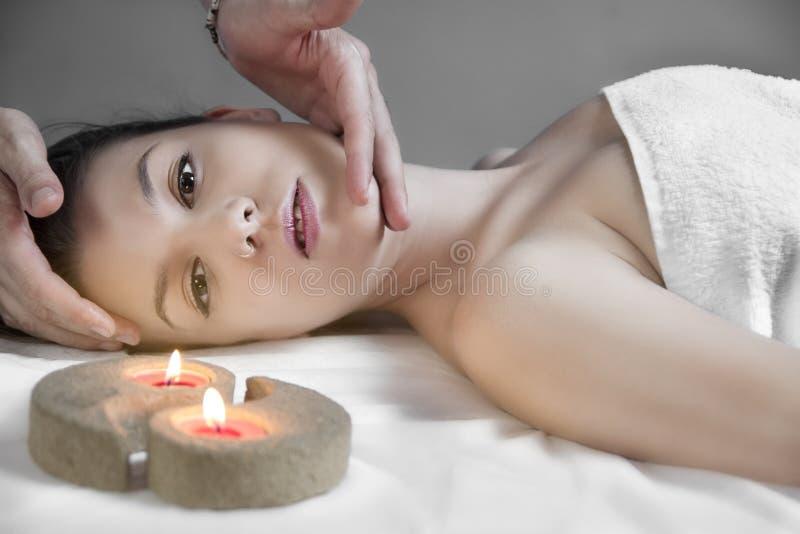 La jeune femme sexy dans la station thermale obtient un massage facial images stock