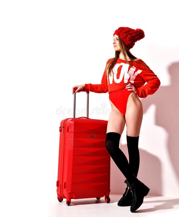 La jeune femme sexy en tissu rouge de corps de mode et le chapeau avec le bagage de voyageur mettent en sac sur le blanc images stock