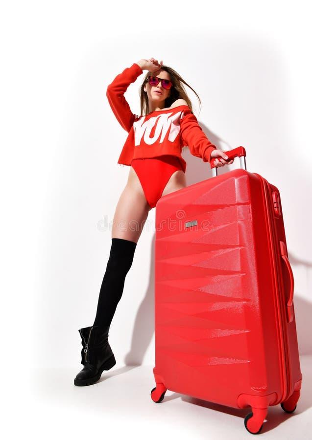 La jeune femme sexy en tissu rouge de corps de mode et le chapeau avec le bagage de voyageur mettent en sac sur le blanc photo stock