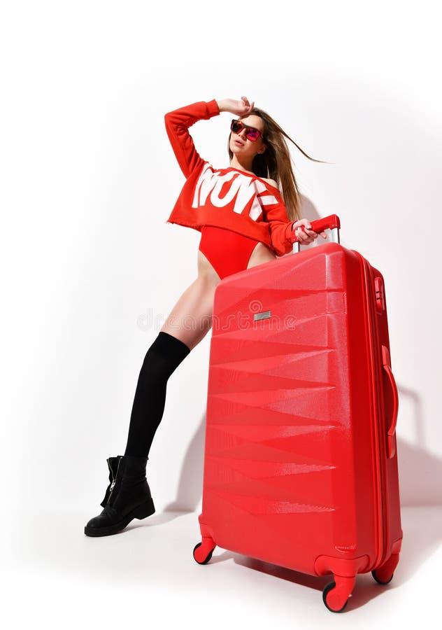 La jeune femme sexy en tissu rouge de corps de mode et le chapeau avec le bagage de voyageur mettent en sac sur le blanc photographie stock