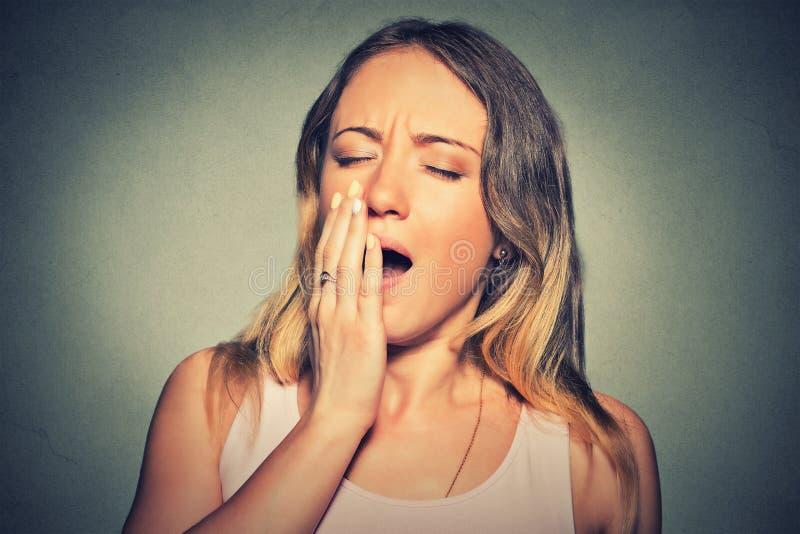 La jeune femme somnolente avec les yeux de baîllement de bouche grande ouverte a fermé sembler ennuyeuse photos stock