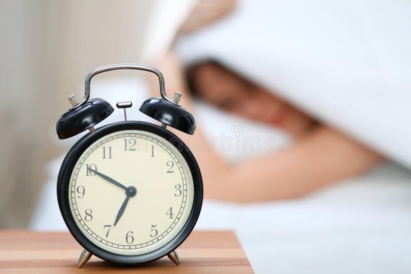 La jeune femme somnolente sous la couverture avec sa tête mettent le ` t veulent se réveiller devant le plan rapproché de réveil  images libres de droits