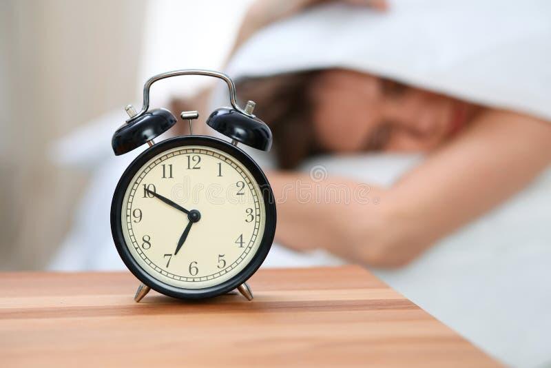 La jeune femme somnolente sous la couverture avec sa tête mettent le ` t veulent se réveiller devant le plan rapproché de réveil  photos libres de droits