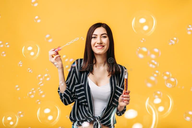 La jeune femme souffle la bulle de savon, fond jaune photographie stock