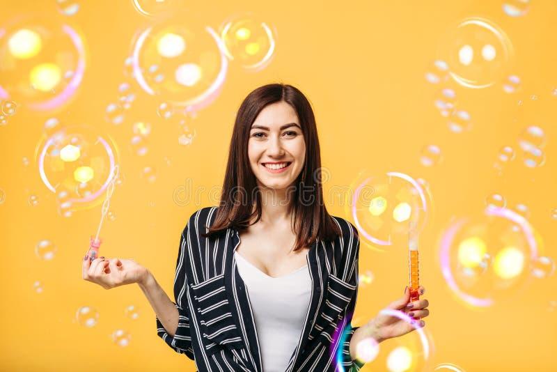 La jeune femme souffle la bulle de savon, fond jaune image libre de droits