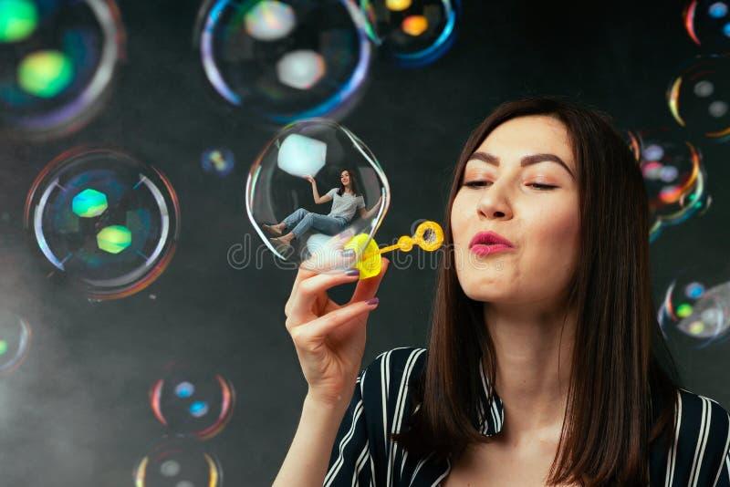 La jeune femme souffle les bulles de savon colorées images stock