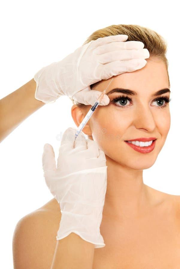 La jeune femme sourie a l'injection faciale de botox image libre de droits
