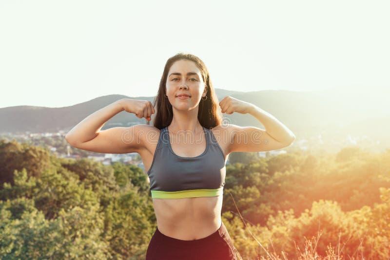 La jeune femme sportive démontre les muscles gonflés des bras À l'arrière-plan il y a une forêt et une vue de la ville photo libre de droits