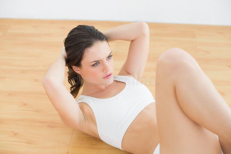 La jeune femme sportive d'ajustement que faire se reposent se lève dans le studio de forme physique photographie stock