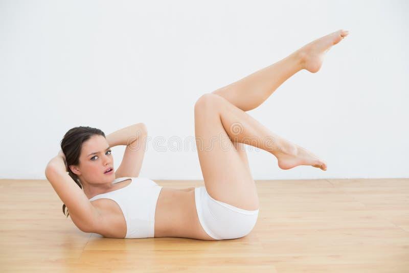 La jeune femme sportive d'ajustement que faire se reposent se lève dans le studio de forme physique photo libre de droits