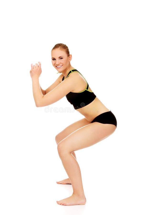 La jeune femme sportive exécute des postures accroupies images stock