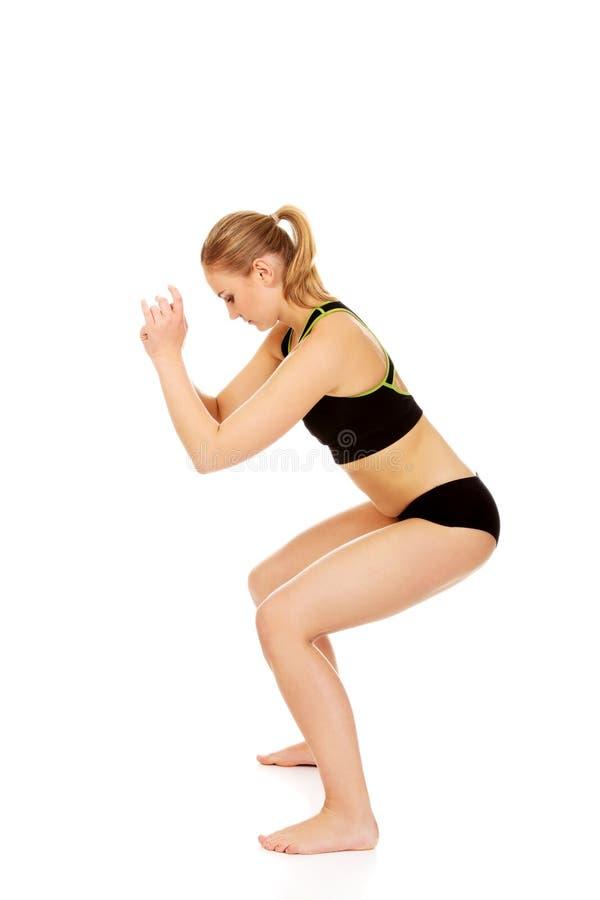 La jeune femme sportive exécute des postures accroupies photos stock