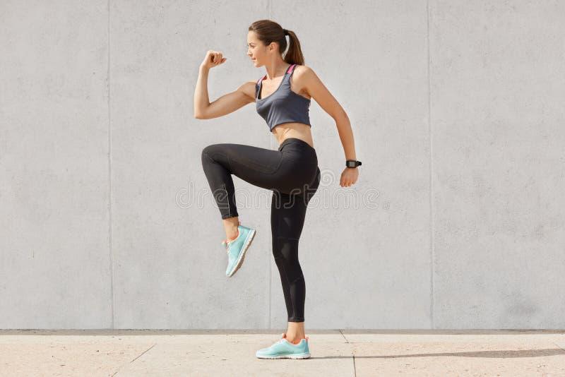 La jeune femme sportive faisant l'exercice sur le fond gris, a habillé supérieur, leggins, espadrilles, a la queue de poney, soul photo stock