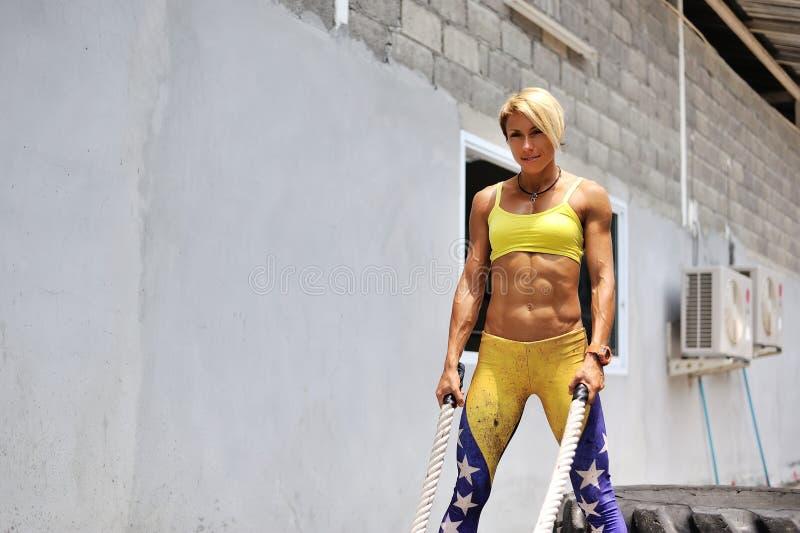 La jeune femme sportive faisant un certain crossfit s'exerce avec une corde o images libres de droits