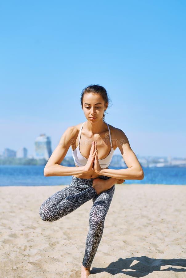 La jeune femme sportive mince fait des exercices de yoga et d'équilibre sur la plage de sable avec le fond de ville Style de vie  image libre de droits