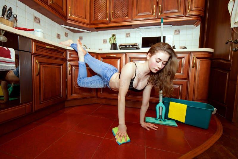 La jeune femme sportive nettoie l'appartement photos libres de droits
