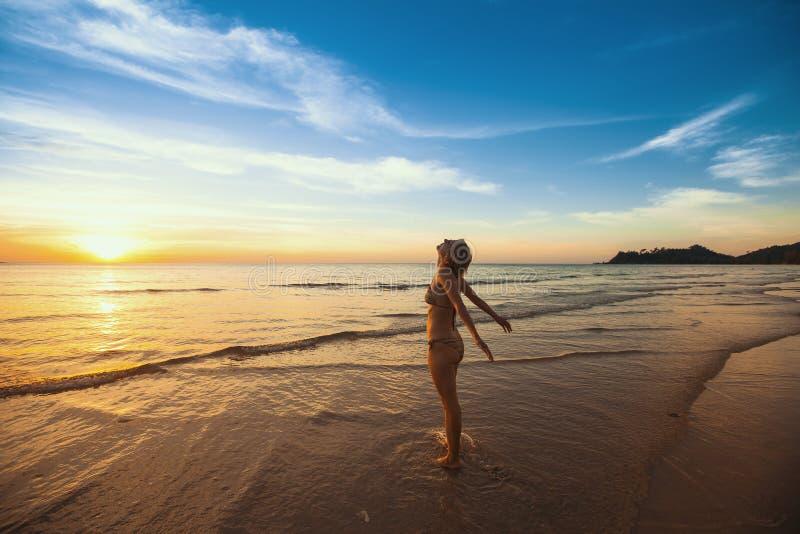 La jeune femme sur la plage est vers le soleil photo libre de droits
