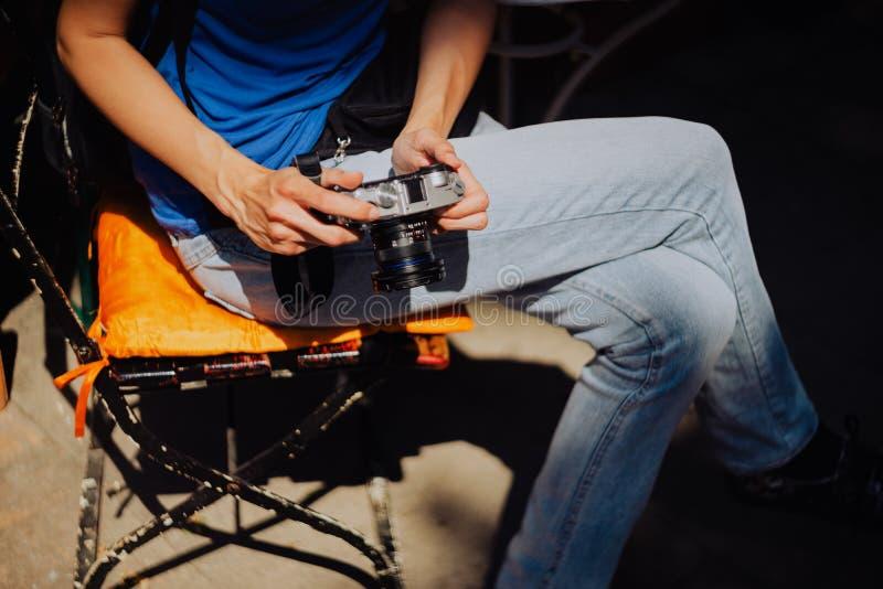 La jeune femme tenant l'appareil-photo de vintage dans des ses mains et vérifiant des photos faites dans la ville voyagent Hambou photographie stock