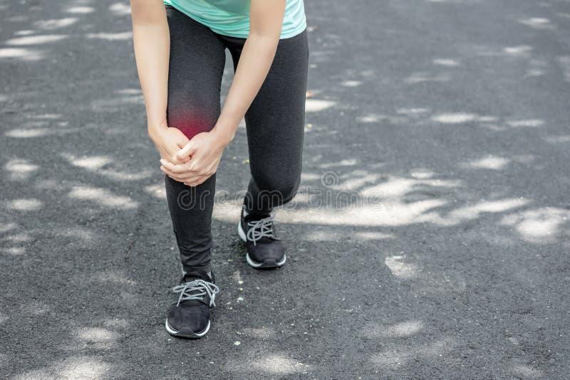 La jeune femme tiennent son genou bless? dans l'ext?rieur photos stock