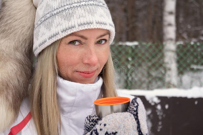 La jeune femme tient dans sa main une tasse d'extérieur de chapeau de thermos de thé un jour givré image stock