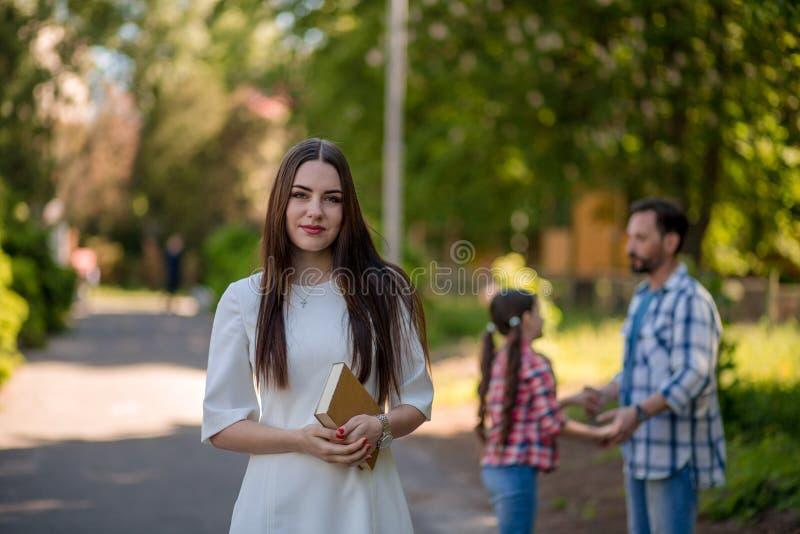 La jeune femme tient le livre tout en se tenant en parc Son Hasband et fille se tenant mains et fabrication photo stock