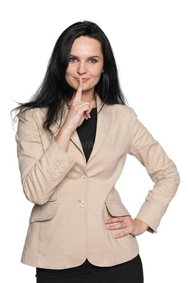 La jeune femme tient un doigt à ses lèvres photo stock